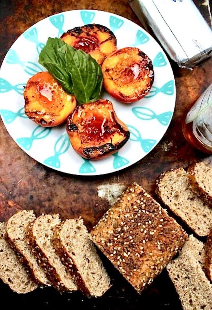 Grilled peaches with toasted bread and block of cream cheese