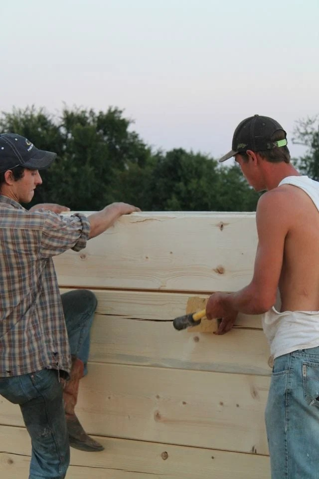 Boys working together to get the perfect fit at the joint of the logs Log Cabin Saturday #2 Miss in the Kitchen