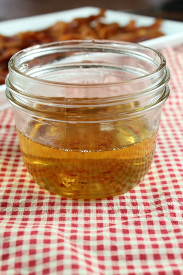 Bacon Drippings in a jar with bacon in the back ground, red gingham cloth under jar