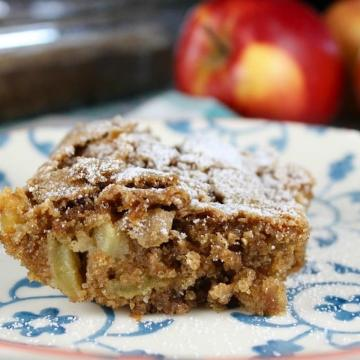 slice of apple cake on a plate, apple in background