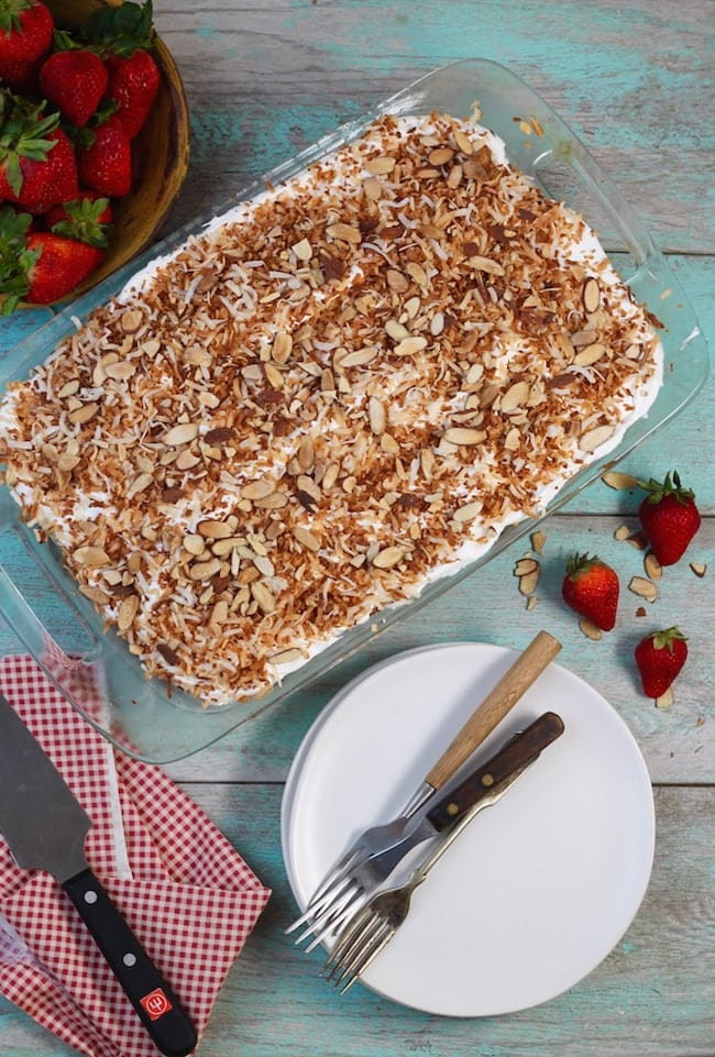 Coconut Cream Cake topped with toasted coconut in a glass baking dish, white plates with forks, whole strawberries and a cake knife on a red check napkin