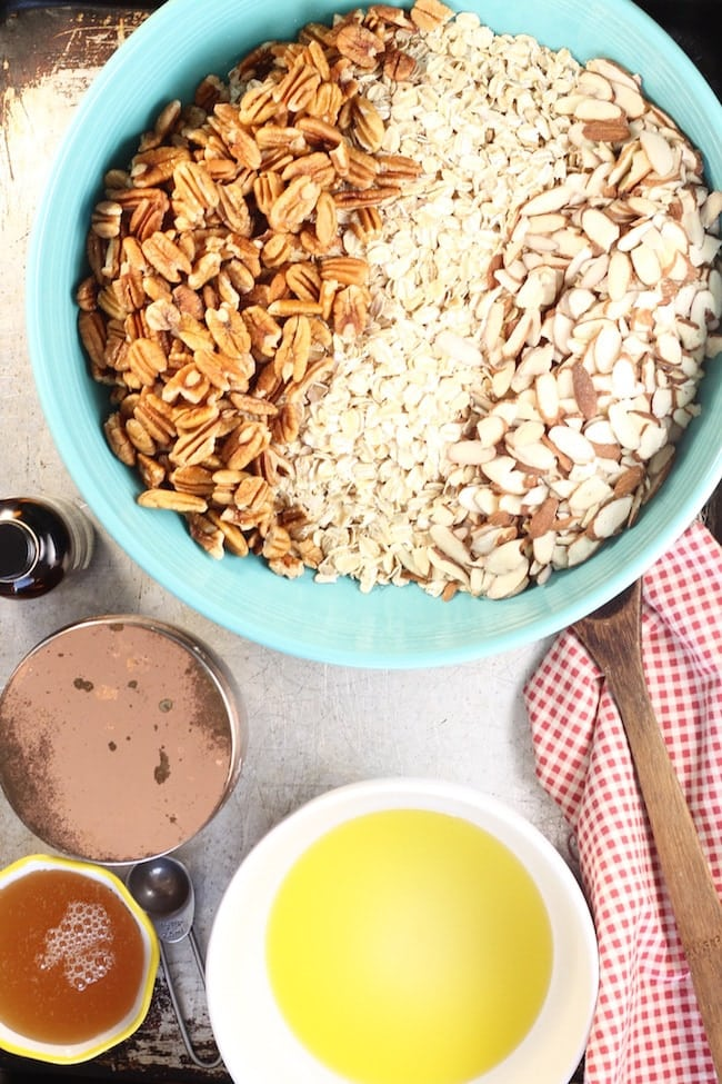 Bowl of old fashioned oats, pecans, and sliced almonds, bowl of olive oil, jar of honey and salt cellar with a red check napkin