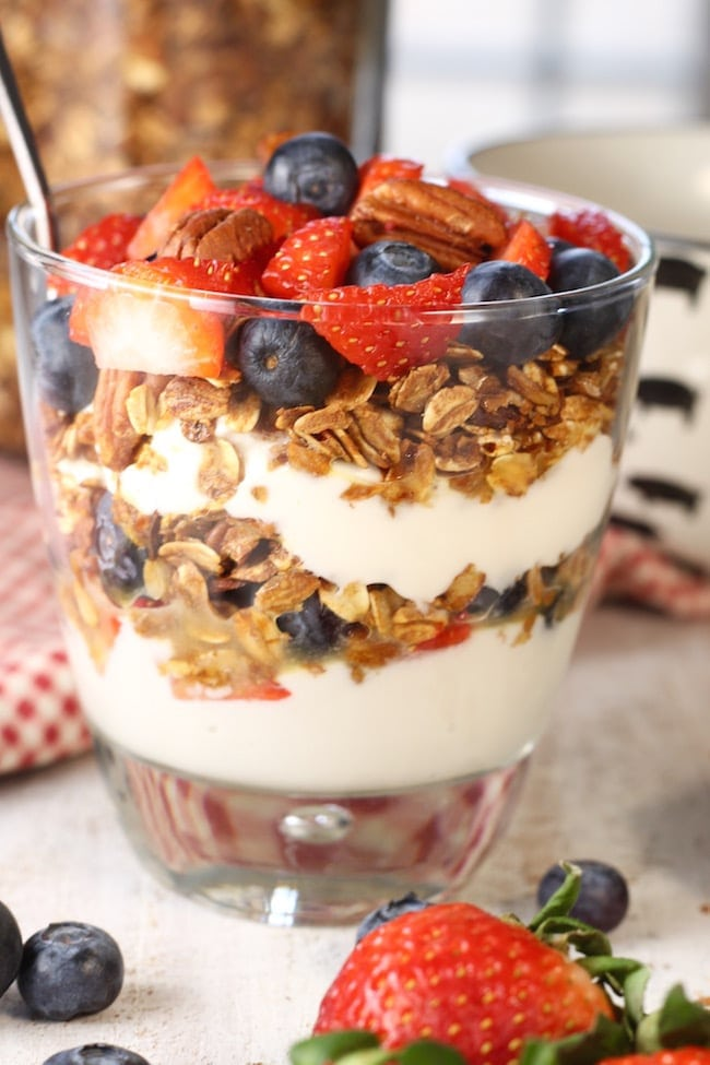 Parfait Glass filled with vanilla yogurt, easy homemade granola, strawberries and blueberries on a white cutting board with red check napkin and fresh berries