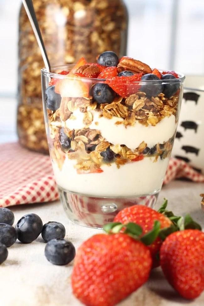 Breakfast parfait with healthy granola, yogurt and fresh strawberries and blueberries
