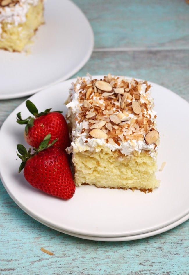 Slice of coconut cream cake, 2 strawberries on a white plate