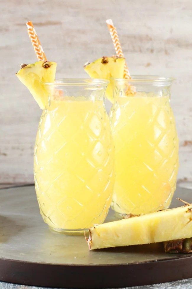 Pineapple Glasses filled with Easy Pineapple Wine Punch garnished with straws and pineapple wedges