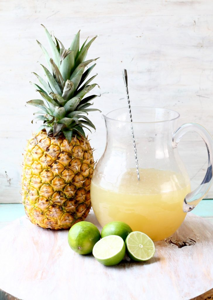 Pineapple Limeade in a pitcher with a fresh pineapple and limes