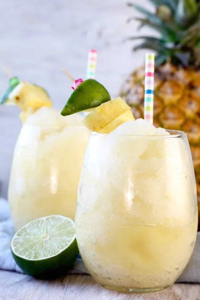 Pineapple Limeade Frozen Slush with a fresh lime half, pineapple in background