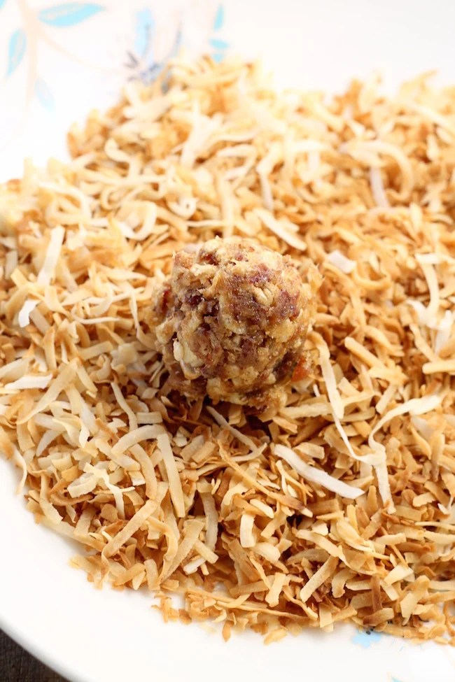 rolling date balls in toasted coconut