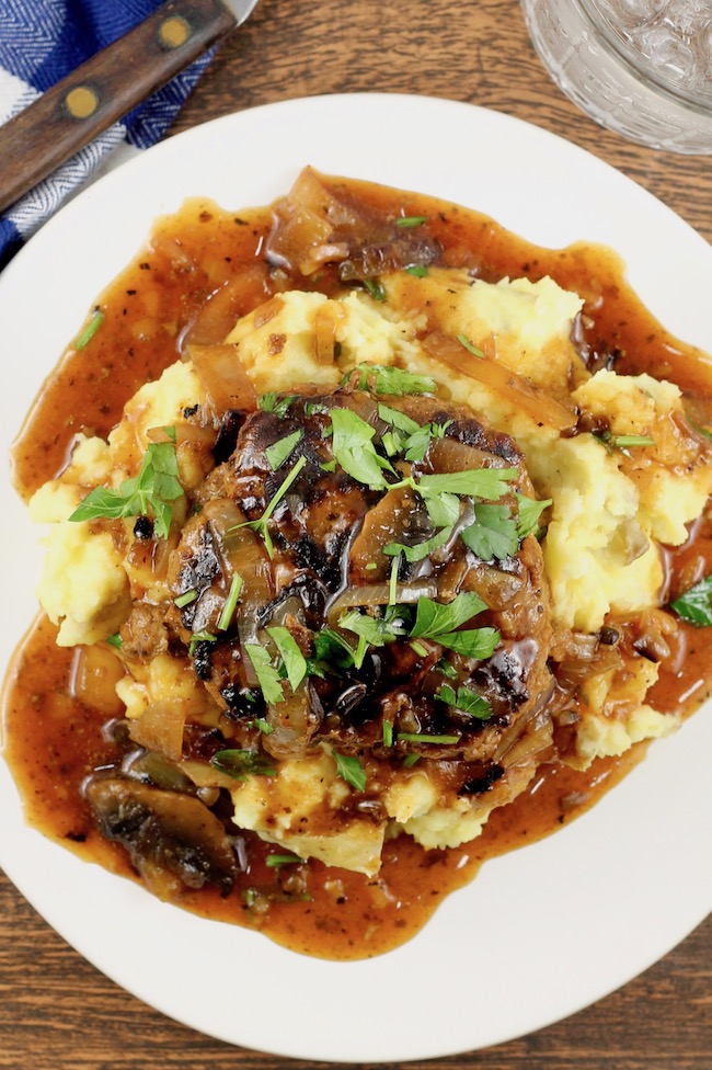 Homemade Salisbury Steak Recipe served over mashed potatoes with mushroom and onion gravy
