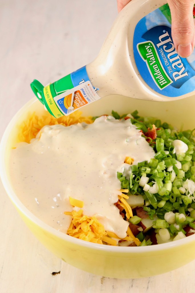 Pouring Hidden Valley Ranch over Red Potato Salad with bacon, cheddar cheese, green onions