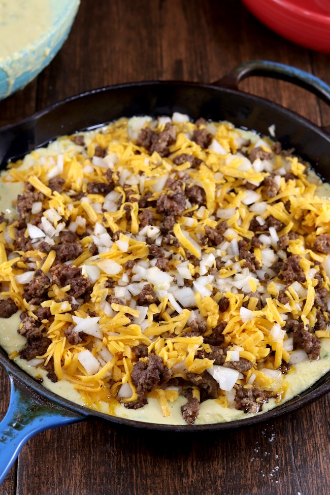 Cooked ground beef, onion, and cheese layer for Mexican Cornbread in a cast iron skillet