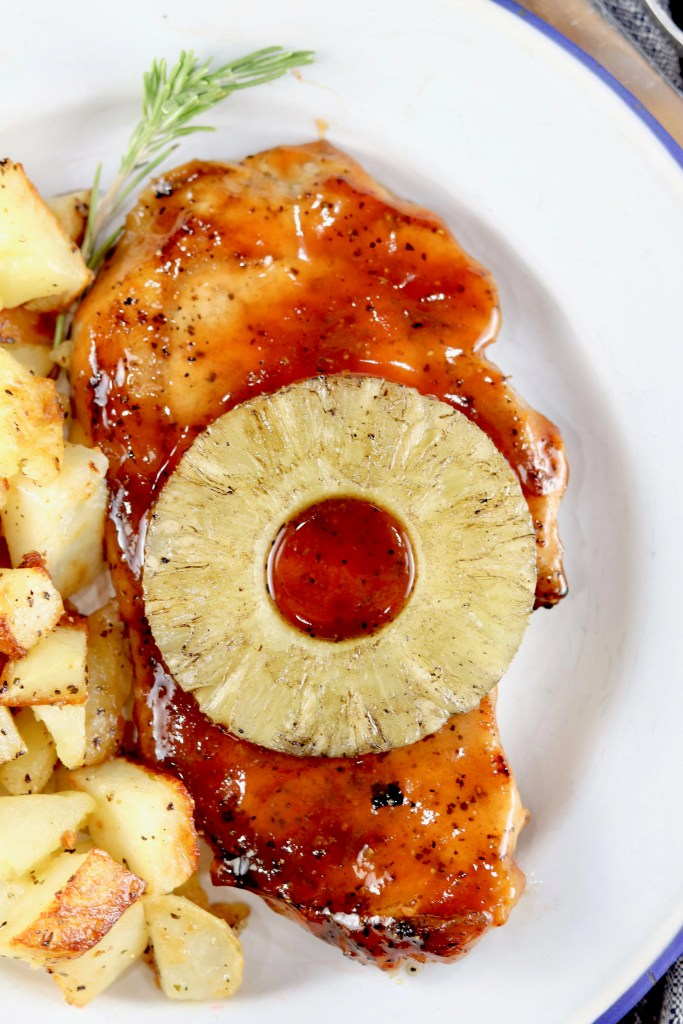 Grilled BBQ Pork Chops topped with a slice of pineapple and potatoes on the side on a white plate