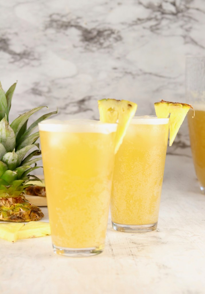Beer Punch in glasses with fresh pineapple garnish