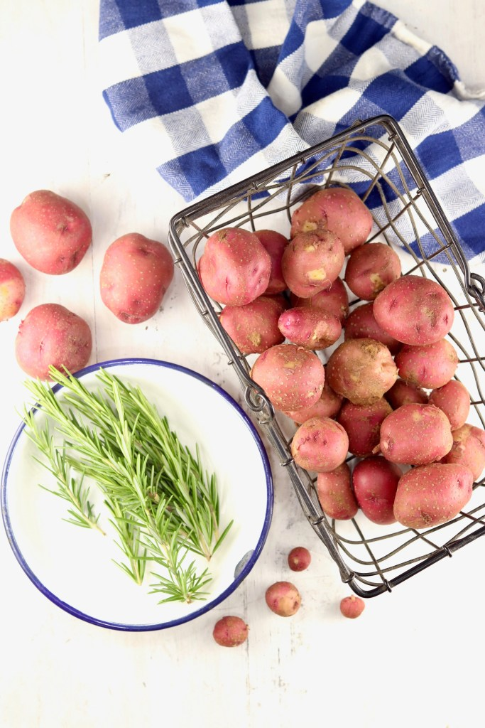 Fresh Rosemary in a white bowl with a wire basket of baby red potatoes