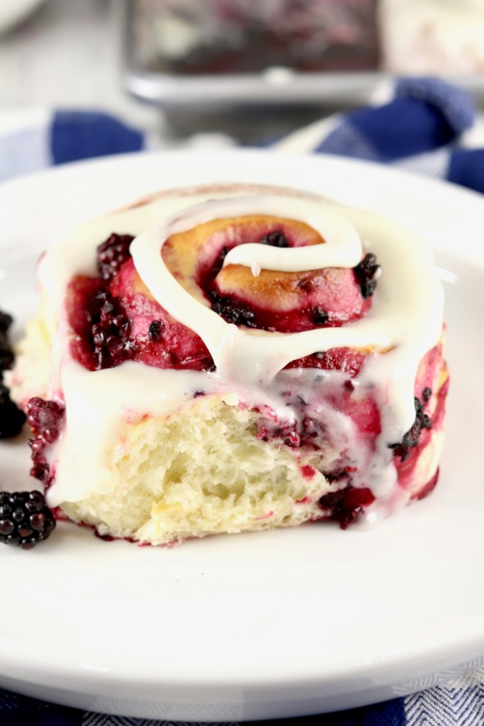 Sweet Roll on a white plate with fresh blackberries. Blue check napkin in background