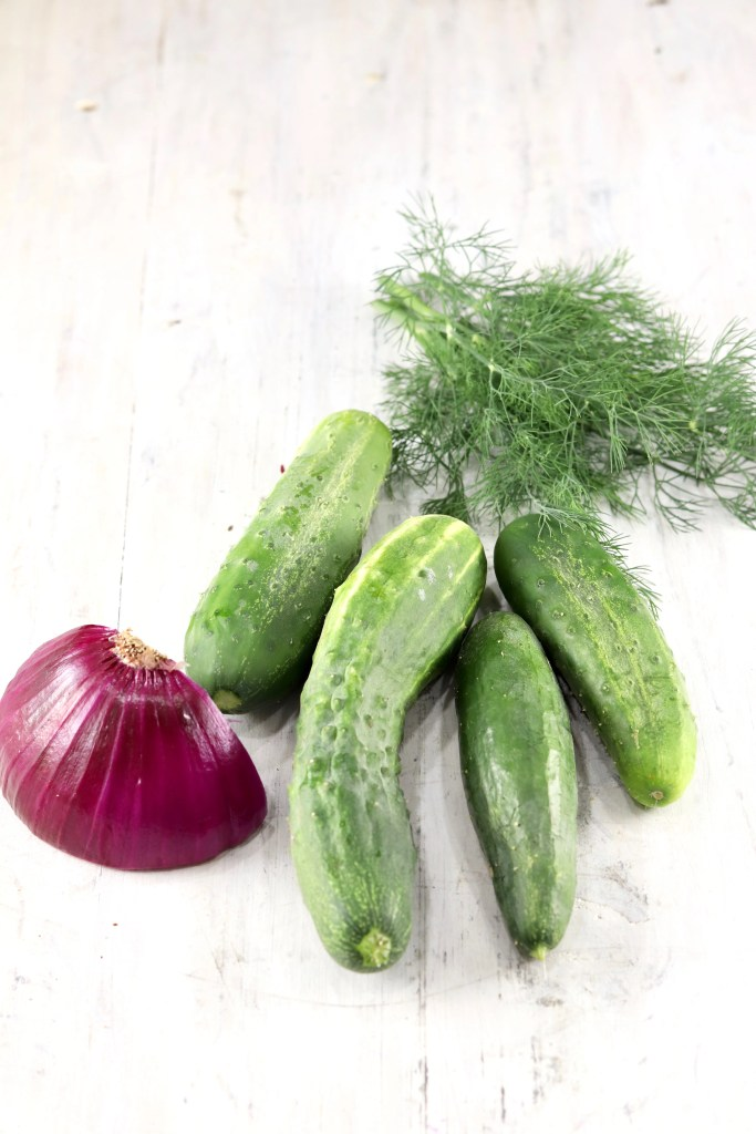 Red Onion, Fresh Cucumbers, fresh dill on a white board