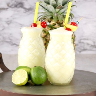 Tray of pineapple glasses with pina colada, fresh line and pineapple in background