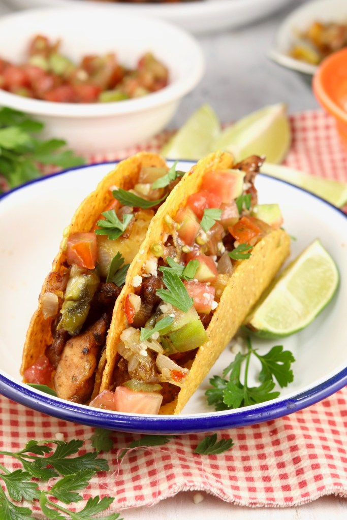 Plate of 2 tacos garnished with cilantro and a lime slice
