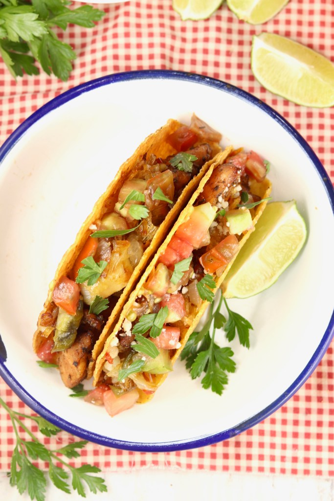Overhead view of fish tacos with tomatoes on a white plate