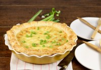 Bacon Quiche in a yellow pie plate garnished with green onions