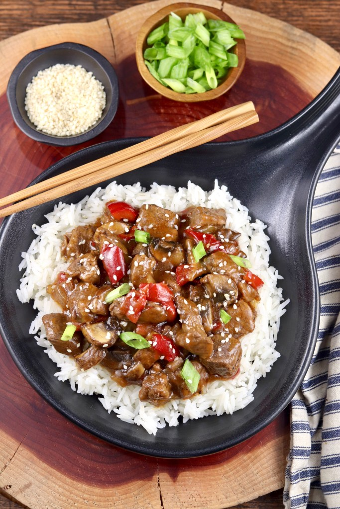 Black skillet with Teriyaki Steak over rice, bowl of green onions and bowl of sesame seeds