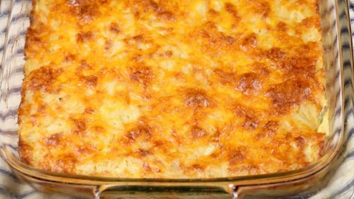 Cheesy Funeral Potatoes casserole in glass baking dish