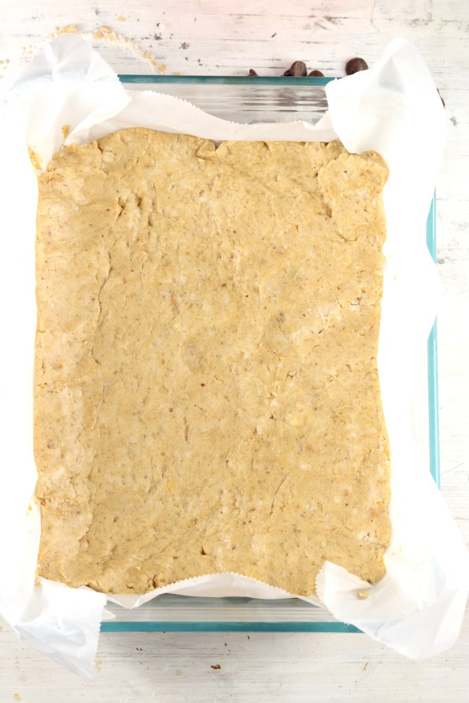 Peanut Butter bars in a parchment paper lined baking dish