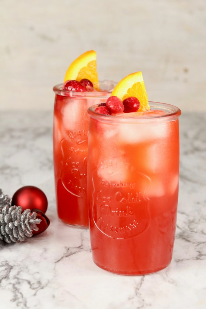 2 glasses of red holiday punch garnished with cranberries