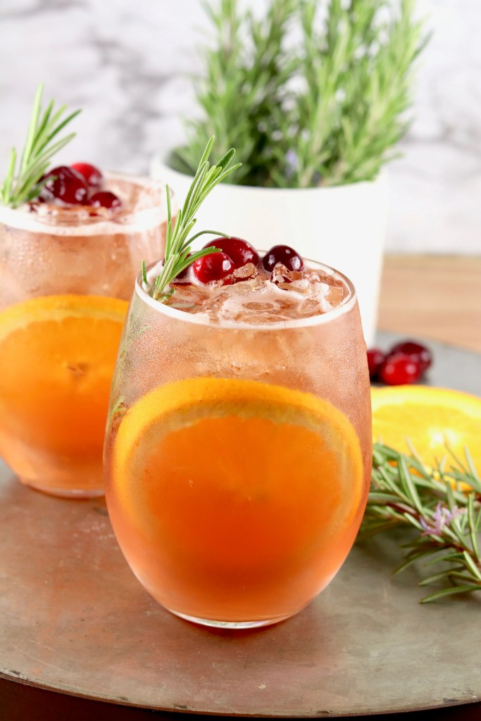 Winter Moscato Cocktail with cranberry and rosemary garnish with an orange slice in the glass
