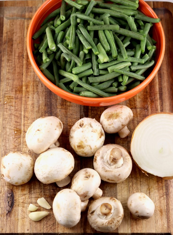 Fresh green beans in an orange bowl, whole button mushrooms and half of an onion
