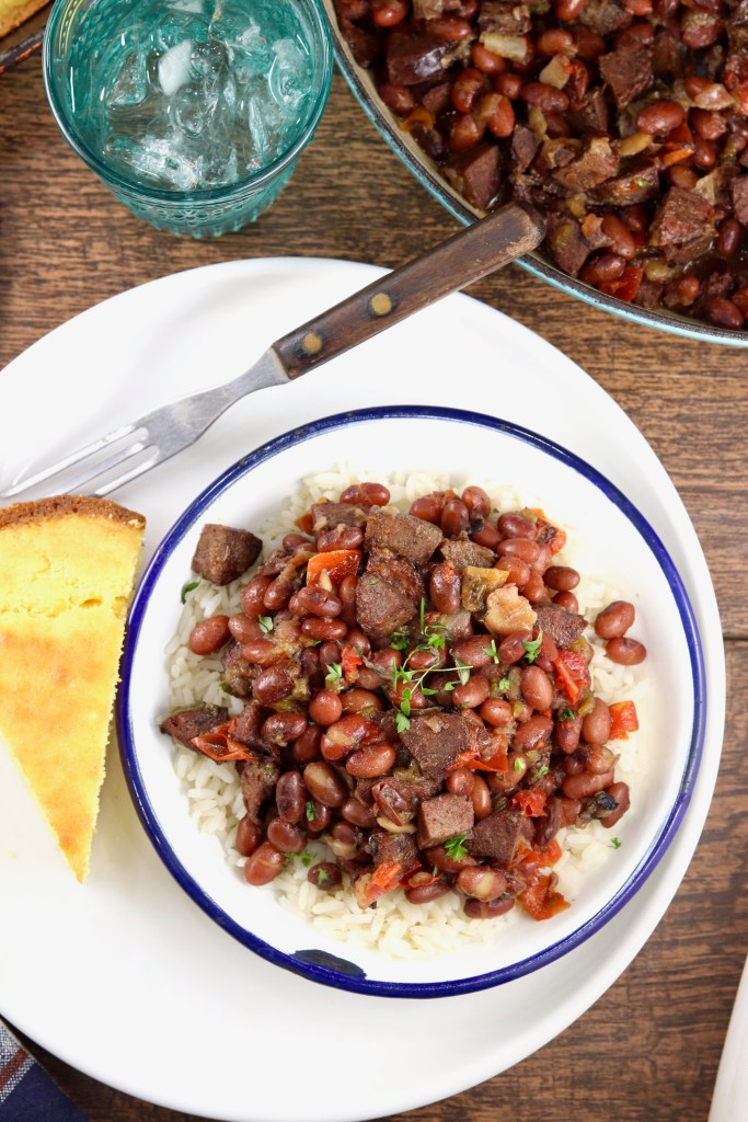 Plate of cornbread with bowl of red beans and rice