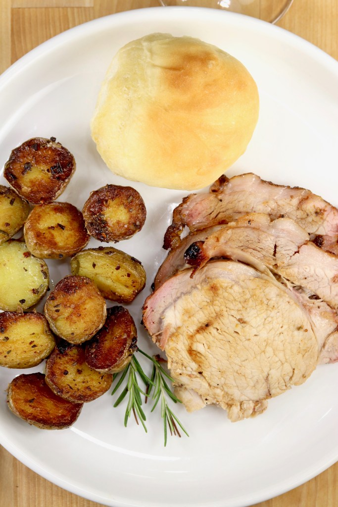 Plate of sliced pork, roasted potatoes and a dinner roll