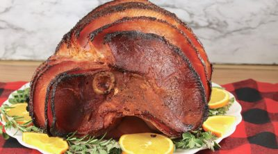 Maple Glazed Ham on a platter with fresh herbs and orange slices