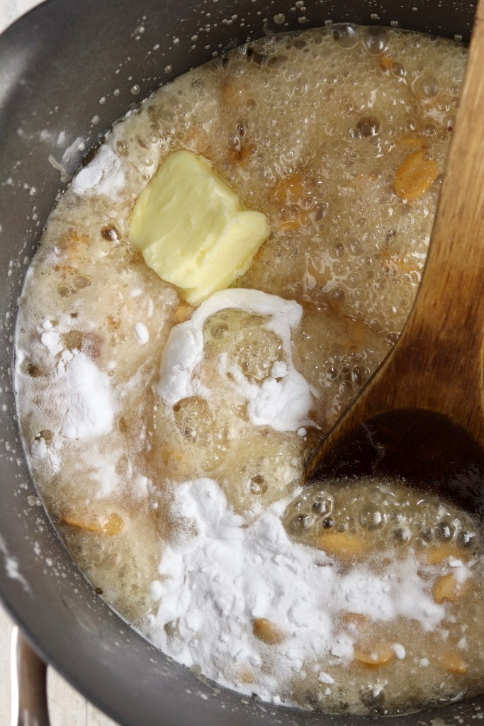 Adding butter and baking soda to peanut brittle mixture