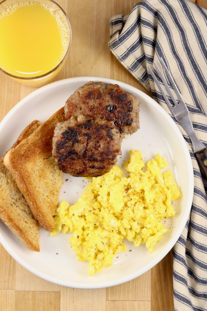 plate of breakfast sausage, scrambled eggs and toast, glass of orange juice