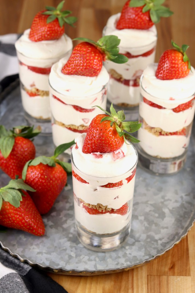 Tray of layered cheesecake parfaits with strawberry garnish