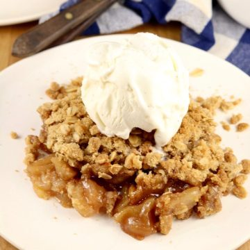 apple crisp with a scoop of vanilla ice cream on a small plate