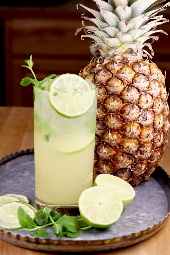 Pineapple Mojito cocktail with a fresh pineapple and lime slices