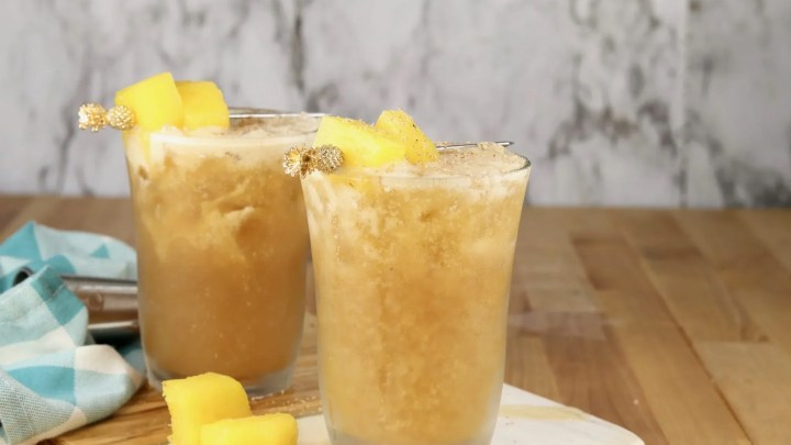 2 Painkiller cocktails with pineapple garnish