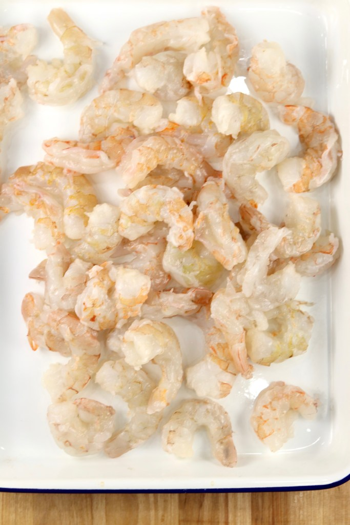 Raw Large shrimp, peeled on a white enameled baking dish