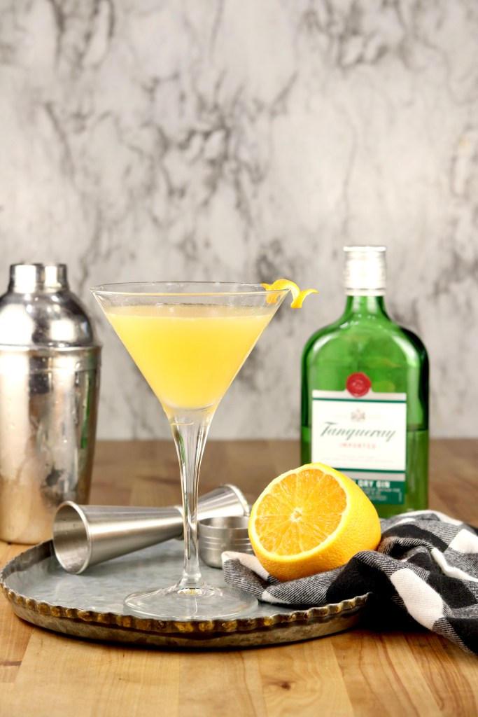 Bees Knees Cocktail in a Martini Glass with a lemon twist, Bottle of Tanqueray Gin, half of a lemon and a cocktail shaker on a tray