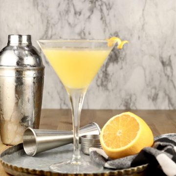 Bees Knees Cocktail in a martini glass with cocktail shaker and a lemon half