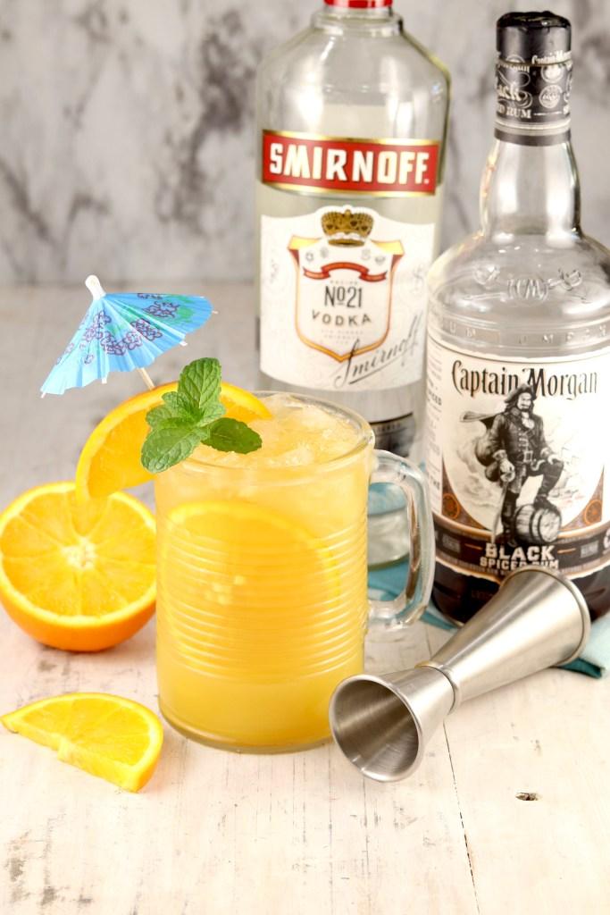 Brass Monkey Cocktail with vodka & rum bottles, jigger