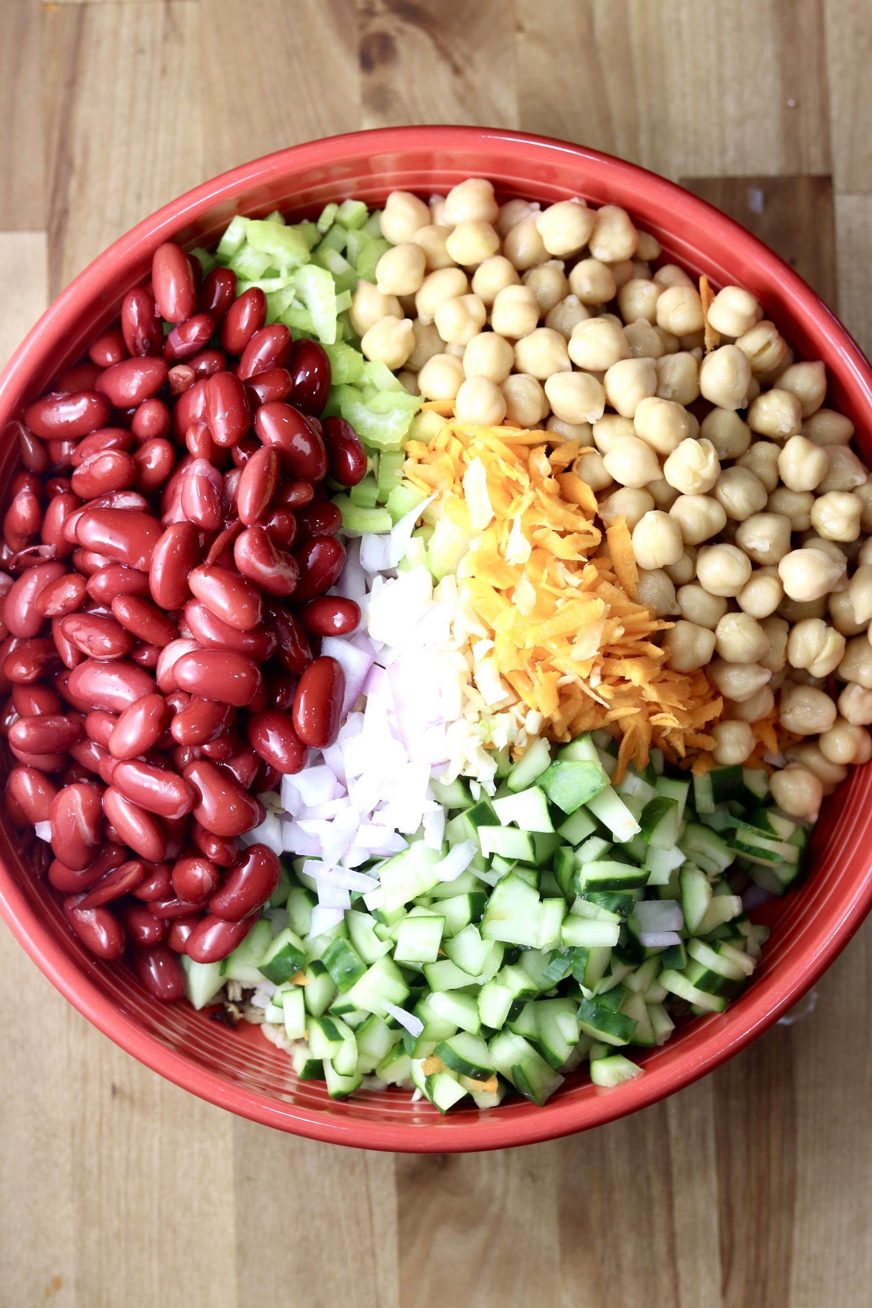 Kidney Beans, chickpeas, cucumbers, carrots, onions and celery in a red bowl