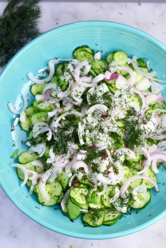 Sliced cucumbers, red onion, fresh dill and red pepper flakes in a blue bowl