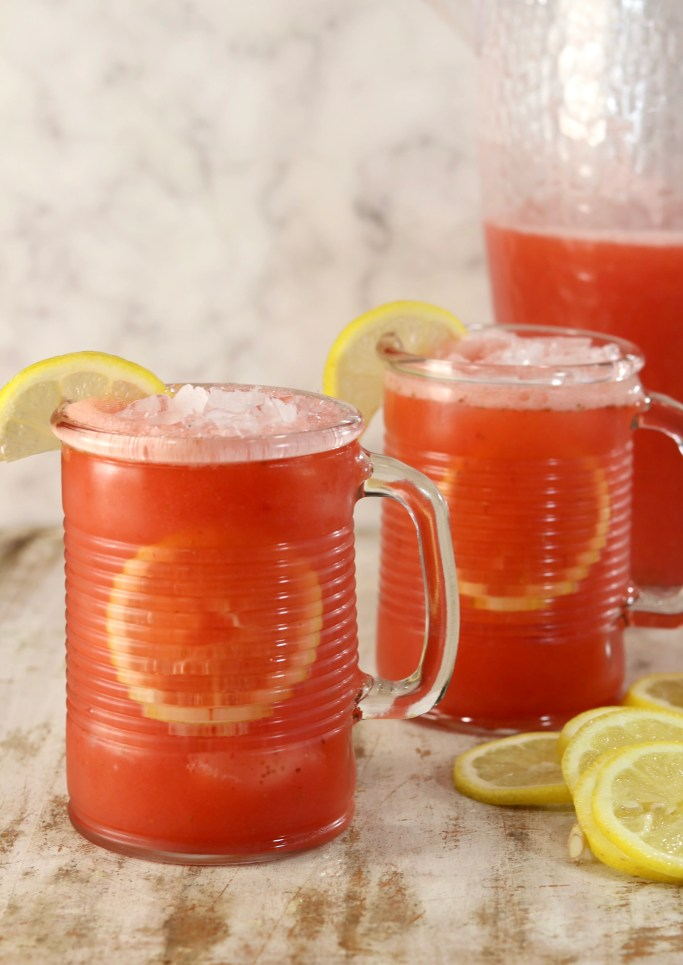 Strawberry lemonade in 2 mugs with pitcher in the background