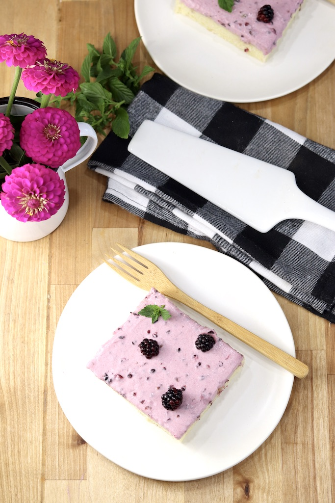 Blackberry Sheet Cake overhead view of a plated slice, pink zinnias in a vase, black and white napkin