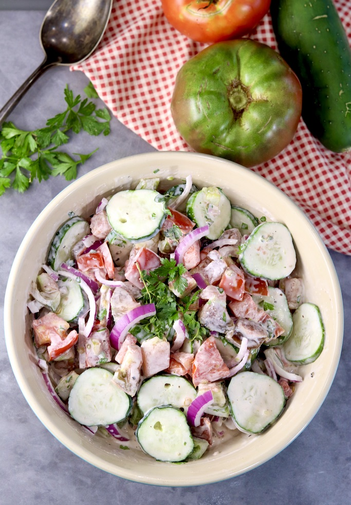 Creamy cucumber tomato salad in a bowl, fresh tomatoes, herbs and cucumbers along side with serving spoon and red napkin