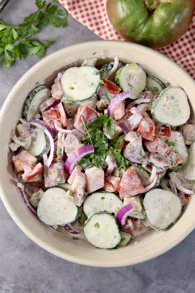 Overhead view of cucumber, tomato, onion salad with creamy dressing